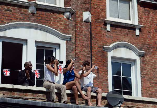 Londoners watch the proceedings as the Olympic flame is carried from Peckham to Kensington during the torch relay.