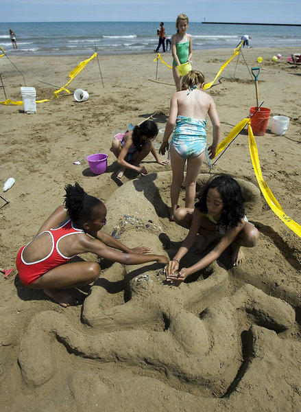 A group from the Daley Bicentennial Park summer camp work on a sand sculpture at 63rd Street beach in Chicago in 2008.