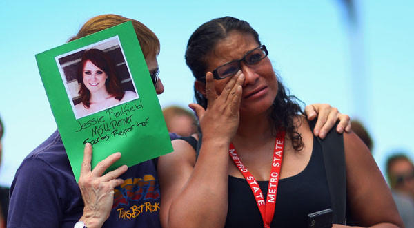 PK McKenzie, left, comforts Stella Ojeda while holding a picture of her former classmate, movie theater shooting victim Jessica Ghawi, during a vigil in Denver.