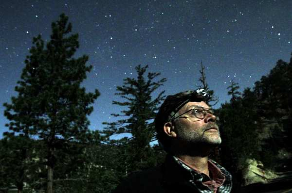 Lance Benner looks into the night sky in the Angeles National Forest in search of owls.