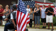 Dozens of mourners gathered outside a Crystal Lake funeral home today as the remains of John Larimer were returned home after the Navy intelligence officer was killed in the Colorado movie theater shooting last week.
