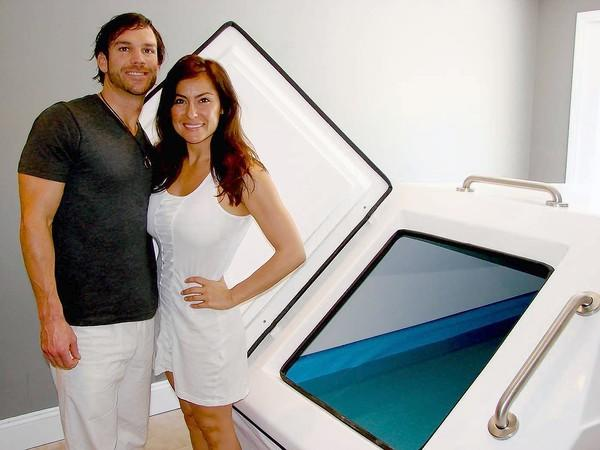 Co-owners of Float Lounge Jeff Brion, left, and Rosanne Ramirez stand next to one of their saltwater tanks. The newly opened Laguna Beach business offers one-hour sessions for users to float and relax in water that's much saltier than the ocean.