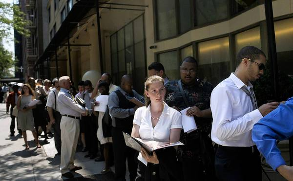 Initial jobless claims fell sharply last week, the U.S. Labor Department says. Above, job seekers at a career fair in New York
