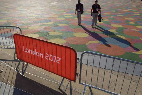 Volunteers for the London 2012 Olympics stroll across Olympic Park on Thursday, a day before the Games open.