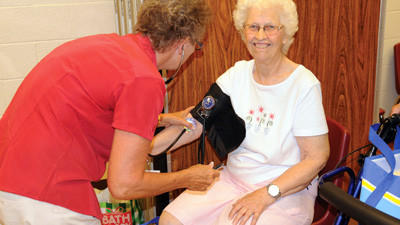 """Fay Furry gets her blood pressure checked by Jane Lowry, a registered nurse at Somerset Hospital. It was Furry's third year attending the Senior Expo at the Somerset County Technology Center. """"It's a wonderful event, I really like it,"""" she said."""