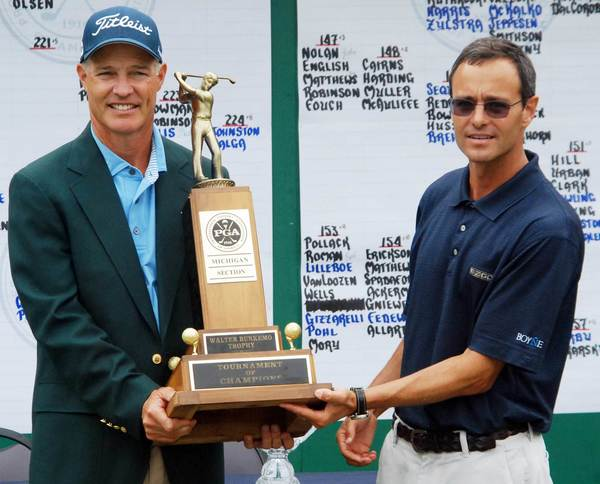 Lee Houtteman (left) of the Grand Traverse Resort & Spa in Acme is presented the Walter Burkemo Trophy by Stephen Kircher, president of Boyne's Eastern Operations, after Houtteman won the Tournament of Champions at Boyne Mountain last year. The annual tournament begins Monday, July 30, at Boyne Mountain.