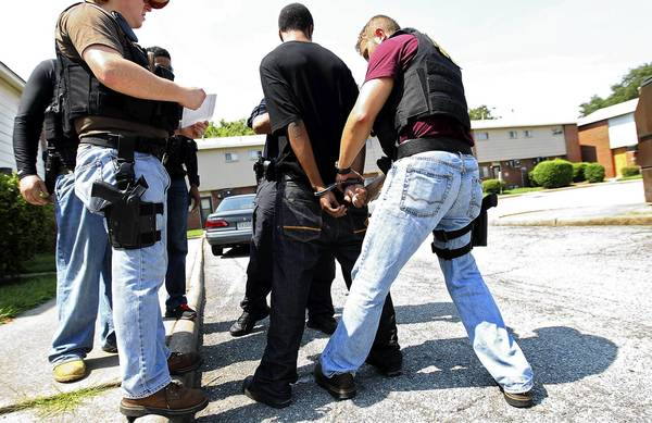 Newport News detective Trevor Pearson searches a suspect after arresting him during a warrant sweep in the Newsome Park area of the city Thursday afternoon.