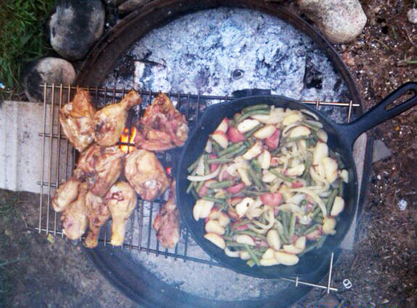 COURTESY PHOTO Heather Hand, of Boyne City, says rustic camping is helped by planning meals around what can be cooked over a fire and in a cast iron pan, like this chicken dinner with roasted potatoes and vegetables.
