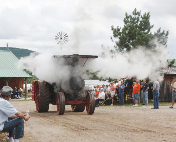 Many different tractors powered down the road during the 25th annual Northern Michigan Antique Flywheelers Show at the Flywheelers show grounds near Walloon Lake. This tractor, circa 1914, blows off some steam during the parade.
