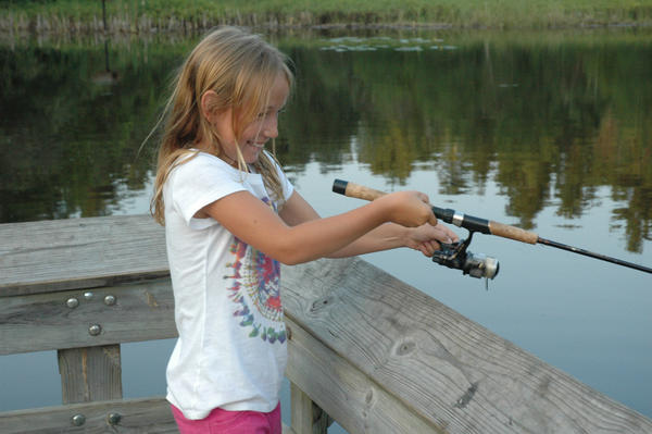 Mailie Witthoeft, 9, of Charlevoix reels in her first-ever fish at Young State Park in Boyne City.