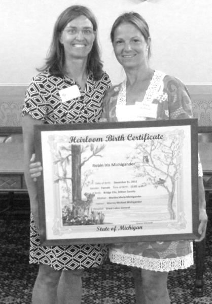 Maggie Kromm (left), executive director of the local Child Abuse Council, congratulates Mary Hramiec Hoffman as a winning artist in the State of Michigan Heirloom Birth Ceritificate program.