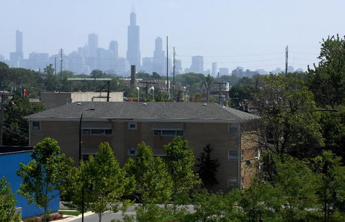 The Chicago skyline is silhouetted in the morning heat. Commuters have a short ride to the Loop from Interstate Highway 55 on the south and Interstate Highway 290 on the north.