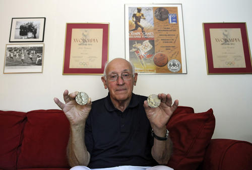 Lindy Remigino holds the two gold medals he won during the 1952 Olympics in Helsinki, one for the 100 meters and the other for the 400 meters relay. Other Olympic memorabilia including the finishline photo of the 100 meters on the left.