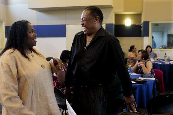 Keris Myrick, left, talks with Roy Anthony Brown, right, director and trainer of Vet to Vet before the Empowerment Congress Mental Health Committee gets underway in Los Angeles. Myrick was a featured speaker at the event.