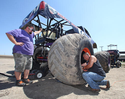 "Steven Hill, driver of the monster truck ""Monkey N Around"", left, watches as pit crew member Clint Watson takes the lug nuts off of a wheel Friday as they performed maintainance on the truck at the Brown County Speedway. photo by john davis taken 7/27/2012"