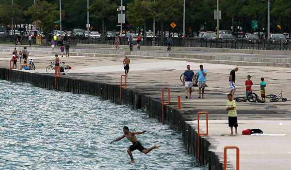 People swim in Lake Michigan where Chicago Park District lifeguards rescued a man near Burton Place on Friday. The man later died.