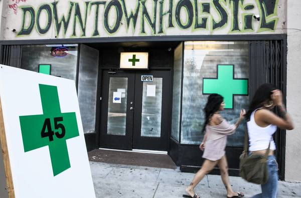 Pedestrians walk past a medical marijuana dispensary in Echo Park on Tuesday, when the Los Angeles City Council voted to ban pot shops.
