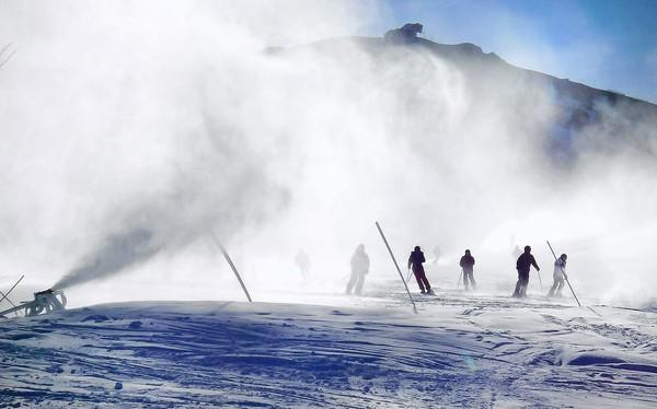 Skier and snowboarders glide through a man-made blizzard as cold daytime temperatures allowed snow making at Mammoth Mountain in January. A trade group said that participation in snow sports dropped during last winter season by about 6%, because of family and work obligations, and a lack of snow.