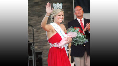 Kelsey Way waves to the crowd in East Park Friday, July 27 shortly after being named the 2012 Miss Charlevoix Venetian Queen as her farther Barney Way applauds in the background.