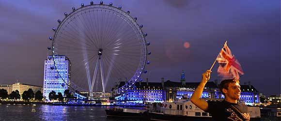 A man holds a British flag as an illuminated London Eye is seen in the background during the opening ceremony of the London 2012 Olympic Games in London on July 27, 2012.