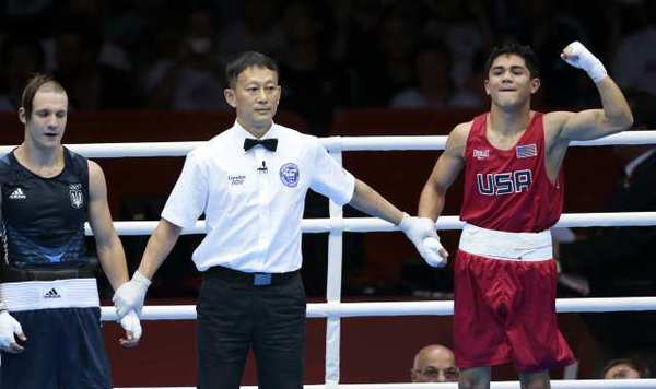 Joseph Diaz Jr., right, is declared the winner of the opening match of the Olympic boxing competition after dominating Ukraine's Pavlo Ishchenko.