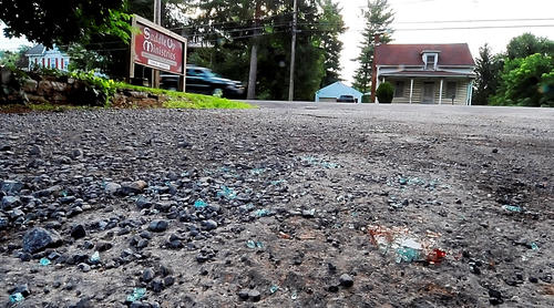 Pieces of broken car window glass can be seen Saturday in the driveway of Saddle Up Ministries in the 7600 block of Anthony Highway in Quincy Township, Pa., after a triple shooting in the area Friday night.