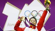 China's Yi Siling holds her gold medal at the victory ceremony after winning the women's 10m air rifle final competition at the London 2012 Olympic Games in the Royal Artillery Barracks at Woolwich in southeast London