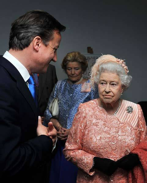Queen Elizabeth speaks to Prime Minister David Cameron as she arrives for the opening ceremony of the London 2012 Olympic Games at the Olympic Stadium.