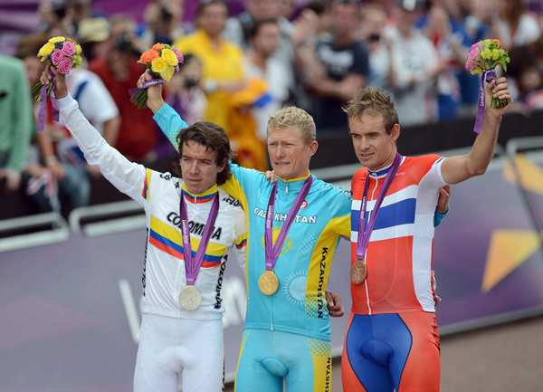 Gold medalist Alexandr Vinokourov of Kazakhstan, center, celebrates with Colombia's Rigoberto Uran, left, and Norway's Alexander Kristoff.