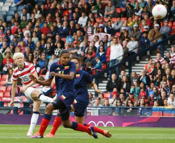 Megan Rapinoe, left, of the U.S. shoots and scores the first goal against Colombia.