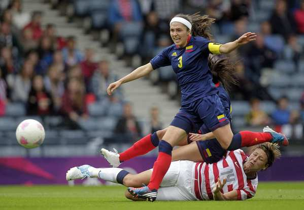 U.S. forward Abby Wambach, on the ground,, scores her team's second goal despite the defensive efforts of Colombia's Natalia Gaitan during the London 2012 Olympic Games.