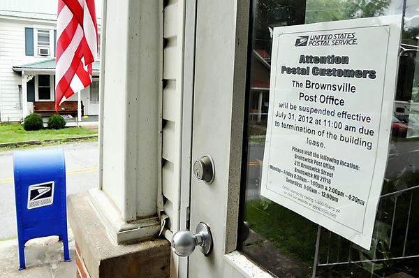 A sign posted on the front door of the Brownsville Post Office notifies customers that the facility is closing July 31.