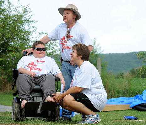Lance Pierce 12, of New Tripoli, was diagnosed with Duchenne Muscular Dystrophy left, along with his mother Christine and father Marshall support the volunteers from the Sons of a Carpenter from the Lehigh Valley, as they work on completion of an addition for an aqua therapy spa for Lance to improve his daily mobility, and muscle strength.