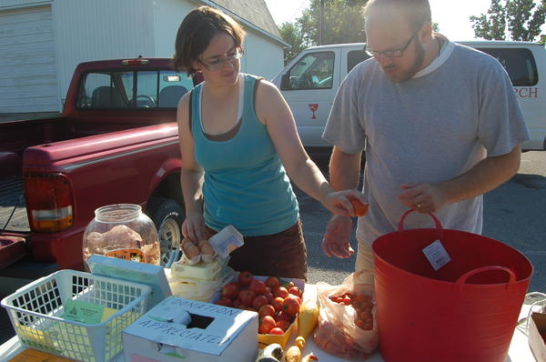 Pastor Josh Snyder and his wife Kate sort produce Saturday at Burgin Christian Church.