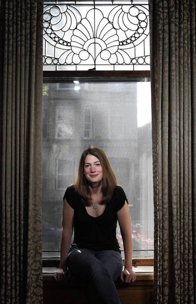 Author Gillian Flynn sits in her living room window