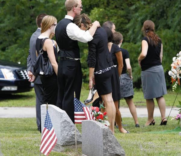 Family and friends pay final respects to Matthew McQuinn, one of 12 killed in the Colorado theater shooting, at a cemetery in Springfield, Ohio