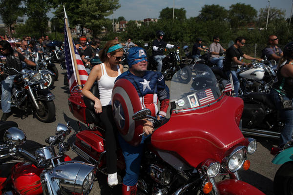 """Lauren Riley sits on the back of a motorcycle driven by Kevin O'Grady, who was dressed as Captain America, before riding in the """"Area 4 Ride to Remember"""" Sunday at 3151 W. Harrison St. in Chicago. The Area 4 Ride to Remember is an annual memorial ride sponsored by the Chicago Police Memorial Foundation, which honors the Chicago Police Department's 562 fallen officers and draws more than 1,000 motorcycle enthusiasts."""