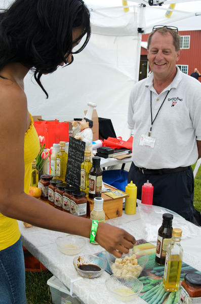 Keisha Champen of Ansonia tries some of the garlic products from Garlic Headz in Torrington. Tom Malahan was there representing the company.