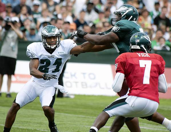 Eagles defensive back Joselio Hanson (21) battles tackle Demetress Bell (77) while trying to get to quarterback Michael Vick during training camp at Lehigh University in Bethlehem on Sunday.