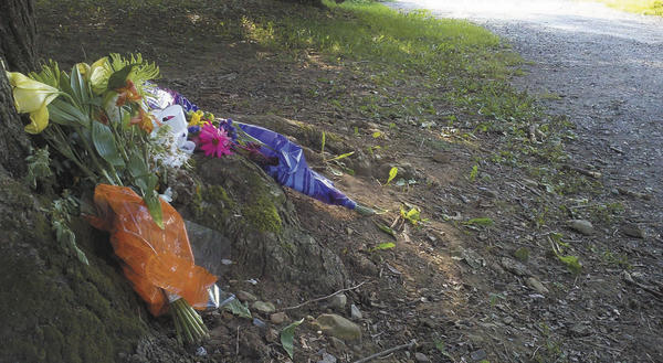 Several bouquets of flowers were left Sunday evening in the driveway of 7705 Anthony Highway (Pa. 997) in Quincy, Pa., where three people were shot and killed Friday night.