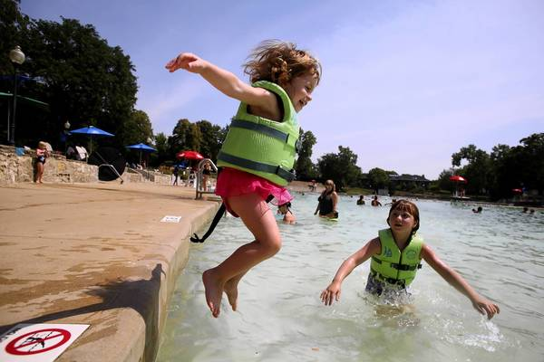 Grace Anderson, 2, of Naperville, jumps into the water as Kendall Banks watches. Her mom, Bridget Anderson, says a life jacket gives Grace confidence as she learns to swim.