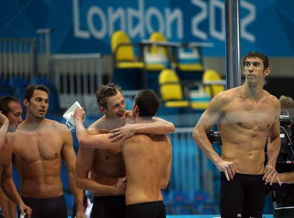 Michael Phelps, right, looks out over the pool as teammate Nathan Adrian congratulates the French gold medalists after the men's 4x100-meter freestyle relay. Team USA won silver in the event.