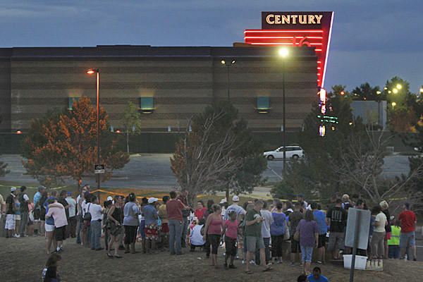 Mourners gather at a memorial across the street from the theater in Aurora, Colo., where a shooting rampage on July 20 left 12 people dead and dozens injured. Some want the theater torn down; others say it should be allowed to reopen.