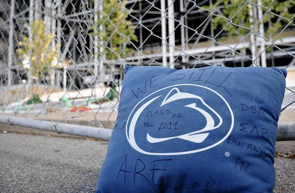 "A pillow that reads ""We still Are..."" leans against the fence where trees have been planted replacing the site that the Joe Paterno statue stood a week ago."