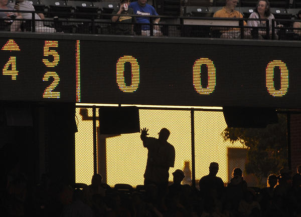 A fan waves to a friend beneath the score board as the Baltimore Orioles trail the Oakland Athletics.