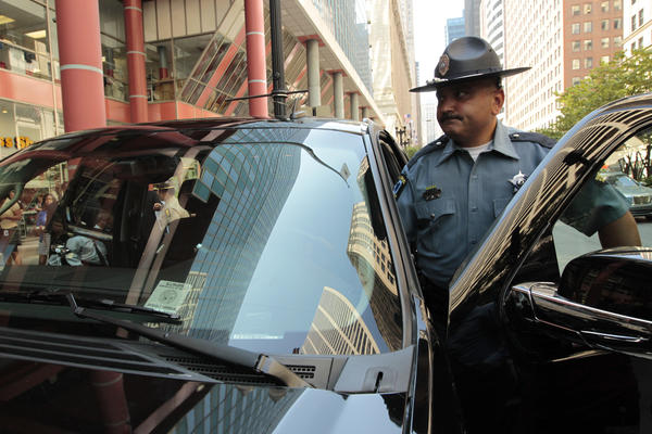 Investigator Elmer Garza, Illinois Secretary of State Police, demonstrates how fake VIN labels were used to steal the vehicle. The scene was at a news conference outside the Thompson Center in Chicago, where authorities announced the arrests of 21 men in an elaborate car-theft ring.