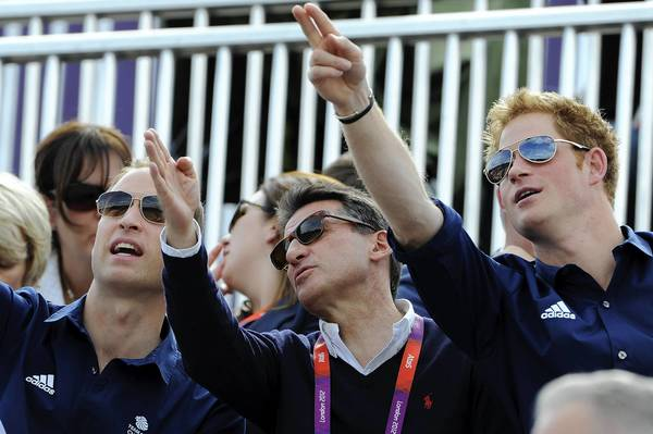 Prince William, Duke of Cambridge, left, LOCOG Chair Lord Sebastian Coe, and Prince Harry watch the Eventing Cross Country Equestrian event.