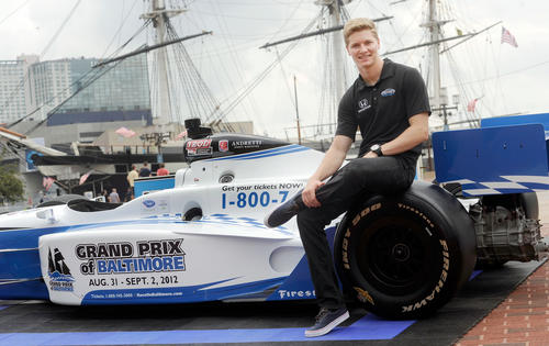 IndyCar driver Josef Newgarden poses on a race car after a news conference to mark the beginning of construction for the Grand Prix of Baltimore in Baltimore.