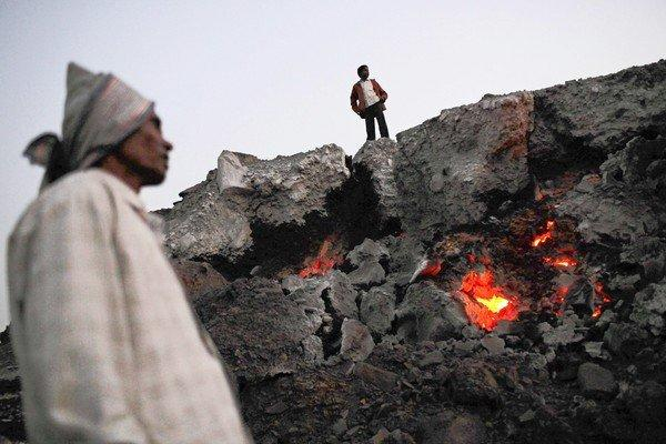 Men stand near the glowing embers of an underground coal fire in Jharia, India, last year.