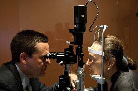Dr. Jose de la Cruz checks Merle Gordon's eyes during a follow-up visit after she had laser surgery to treat her cataracts at the Millennium Eye Center, a satellite clinic of University of Illinois.